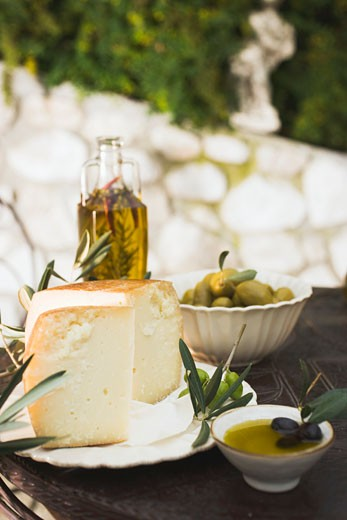 Cheese, olives and olive oil on table out of doors : Stock Photo