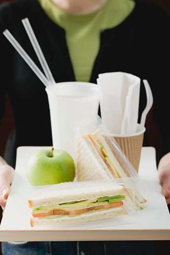 Stock Photo: 1532R-45909 Woman holding sandwiches, apple and drink on tray
