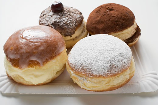 Four different doughnuts on paper plate : Stock Photo