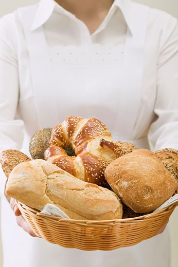 Chambermaid serving assorted bread rolls in bread basket : Stock Photo