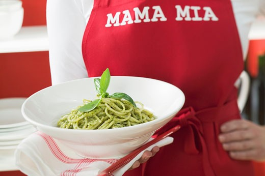 Woman in red apron holding plate of spaghetti with pesto : Stock Photo
