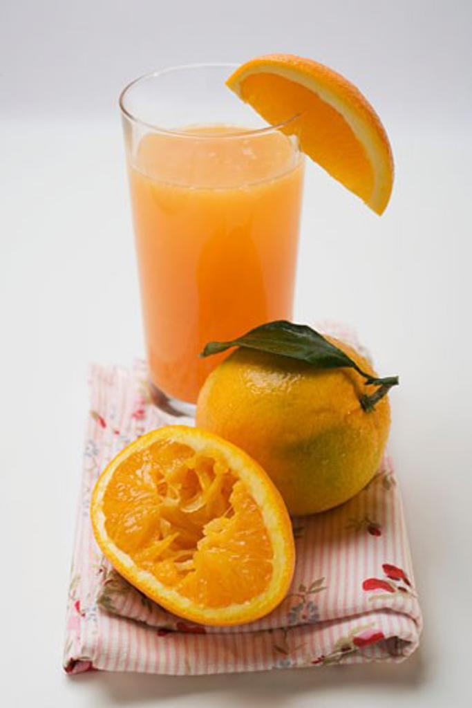Stock Photo: 1532R-46348 Glass of orange juice and oranges
