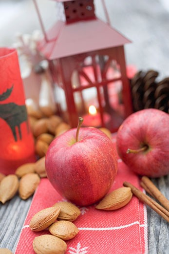 Christmas decoration with apples, nuts, cinnamon & lantern : Stock Photo