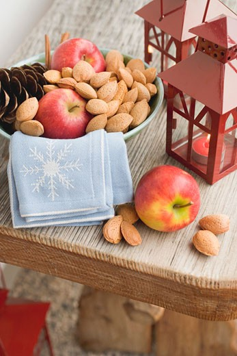 Red apples, almonds and cone in bowl, lanterns beside it : Stock Photo