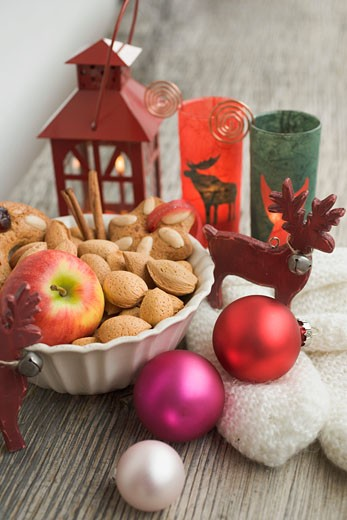 Christmas decoration with apple, nuts, lantern, mittens : Stock Photo
