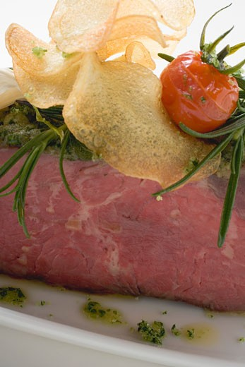Roast beef with pesto crust and potato crisps (detail) : Stock Photo