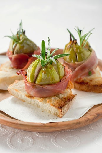 Figs wrapped in raw ham on toast : Stock Photo