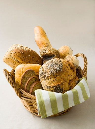 Assorted breads and bread rolls in bread basket : Stock Photo