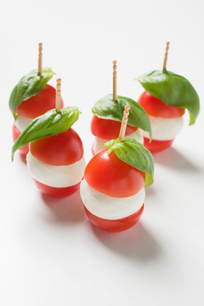 Tomatoes, mozzarella and basil on cocktail sticks : Stock Photo