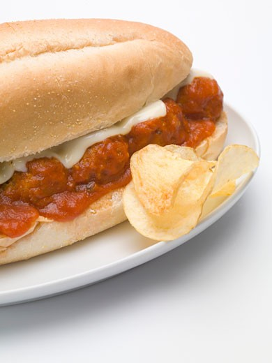 Meatball sub sandwich with tomato sauce and cheese, crisps : Stock Photo