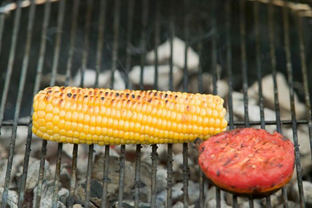 Cob of corn and tomato on a barbecue : Stock Photo