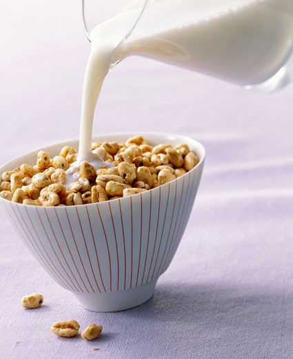 Stock Photo: 1532R-50076 Pouring milk onto honey puffed wheat breakfast cereal