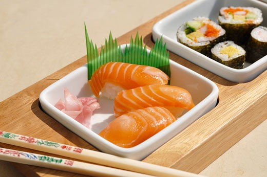 Assorted sushi in dishes with chopsticks : Stock Photo