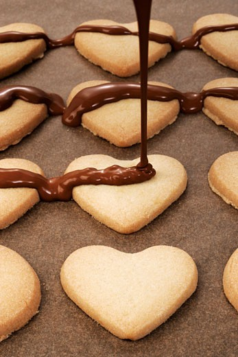 Decorating heart-shaped biscuits with couverture chocolate : Stock Photo