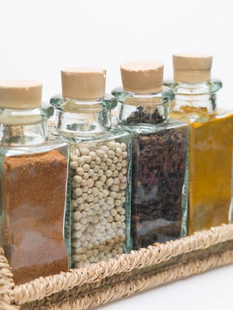 Stock Photo: 1532R-50861 Nutmeg, white peppercorns, cloves & turmeric in spice rack