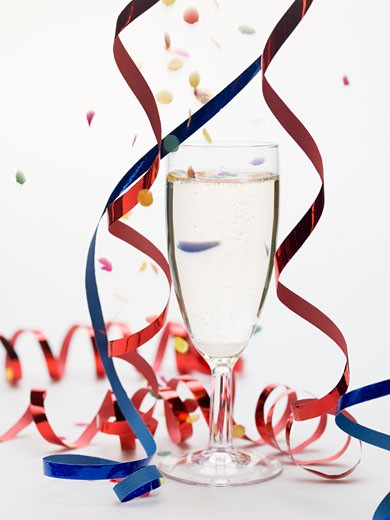 Stock Photo: 1532R-51068 Glass of sparkling wine with party decorations