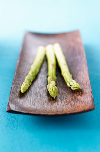 Stock Photo: 1532R-51376 Three spears of green asparagus in wooden dish