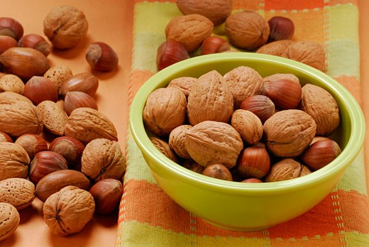 Unshelled walnuts, hazelnuts and almonds in green bowl : Stock Photo