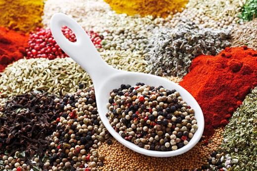 Stock Photo: 1532R-51491 Peppercorns in porcelain spoon on assorted spices