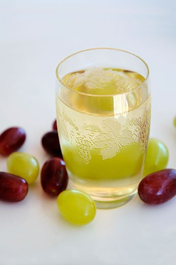 A glass of white wine with grapes : Stock Photo