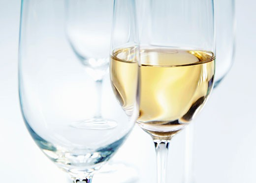 Two empty glasses and a glass of white wine : Stock Photo