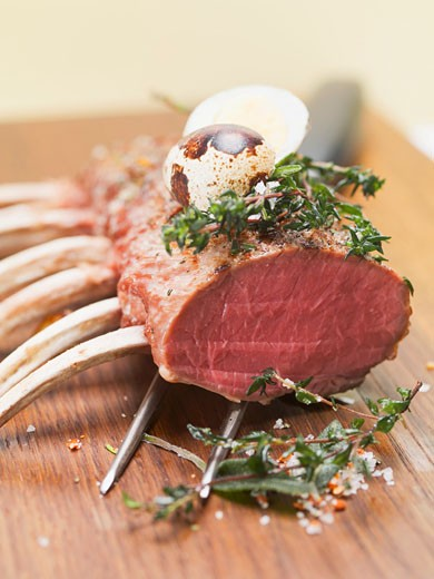 Rack of lamb with herbs and quail's egg : Stock Photo