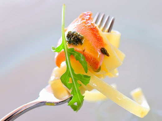 Salmon with fettuccine and pesto on a fork : Stock Photo