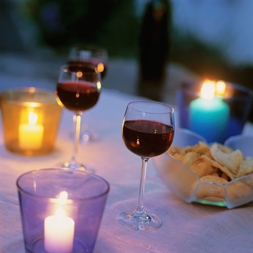 Stock Photo: 1532R-54406 Glasses of red wine and crisps on candlelit table