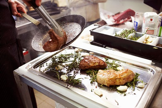 Placing the fried meat on a tray with herbs : Stock Photo