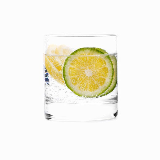 A glass of water with slices of lime : Stock Photo