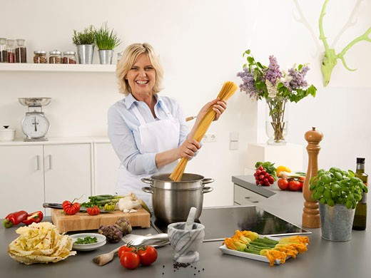 Stock Photo: 1532R-55090 Woman laughing with spaghetti in her hands