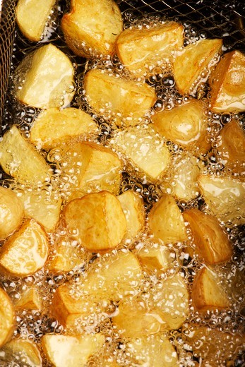 Potatoes being fried in hot oil : Stock Photo
