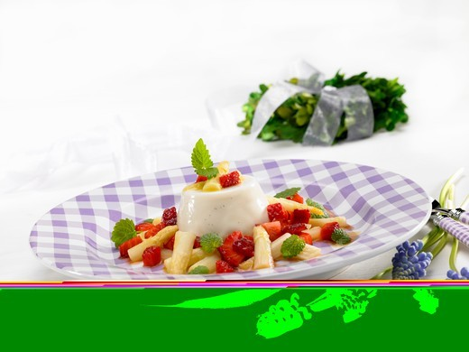 Panna cotta with white asparagus and strawberries and grape hyacinths next to the plate : Stock Photo