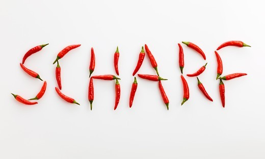 The word 'SCHARF' ('Spicy' in German) written in red chillies : Stock Photo