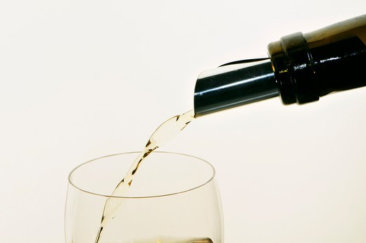Stock Photo: 1532R-56624 White Wine Pouring from Bottle into Glass; White Background