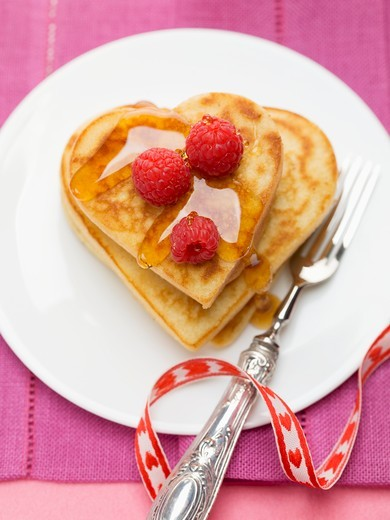 Heart-shaped pancakes with raspberries and maple syrup : Stock Photo