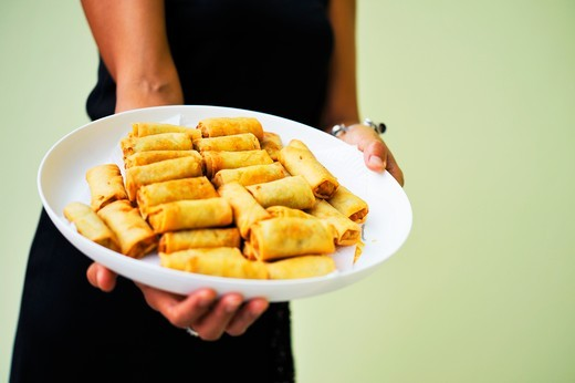 A woman holding a plate of spring rolls : Stock Photo