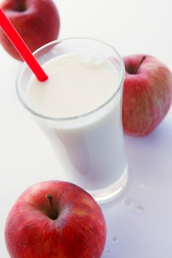 Stock Photo: 1532R-59207 A glass of milk with a straw and three red apples