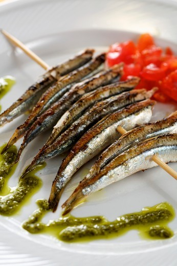 Stock Photo: 1532R-59979 Grilled sardines on a skewer with pesto and tomato salad