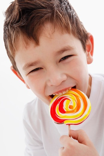 A little boy biting into a lolly : Stock Photo