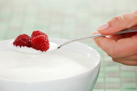 Hand holding a spoon of yogurt with raspberries : Stock Photo