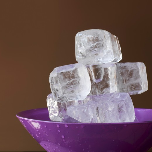 Ice cubes in a lavender colored dish : Stock Photo