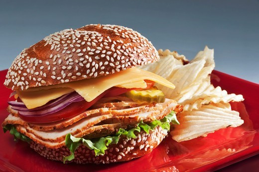Stock Photo: 1532R-61892 Turkey Sandwich on Sesame Seed Roll with American Cheese, Tomato, Onion and Pickle; Chips