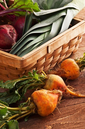 Stock Photo: 1532R-61894 Organic Golden Beets Next to a Basket Filled with Red Beets and Leeks