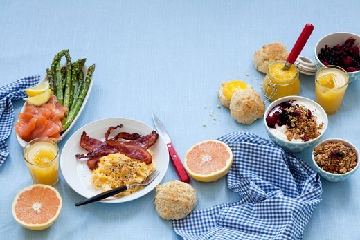 Stock Photo: 1532R-63476 A breakfast table laid with scrambled egg and bacon, salmon, jam, muesli and grapefruit