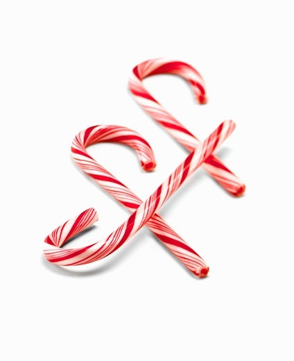Three Red and White Striped Candy Canes on a White Background : Stock Photo
