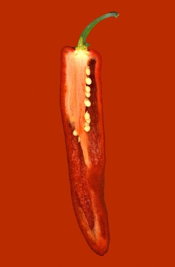 Half a red chilli pepper on a red surface : Stock Photo
