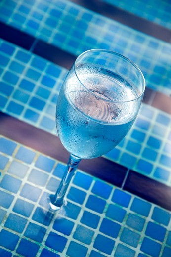 A glass of water by the pool : Stock Photo