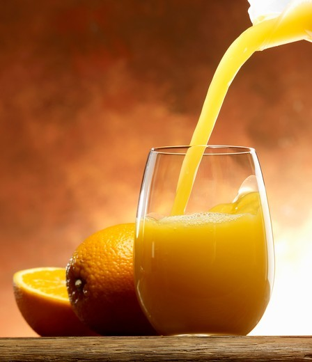 Pouring orange juice into a glass : Stock Photo