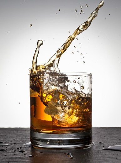 Ice cube falling into whisky glass : Stock Photo